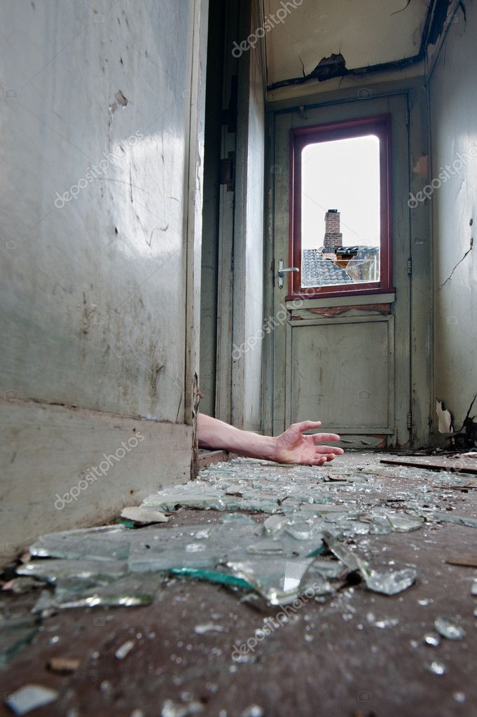 A person lying on the floor inn an old worn-out railway carriage with broken glass on the floor  Stock Photo #5967822