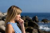 Aantrekkelijke doordachte meisje op rotsachtige strand door zee. — Stockfoto