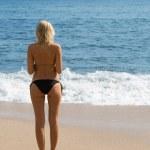 Girl on the sandy beach by the sea. — Stock Photo
