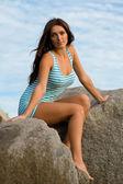海沿いの岩の上のブルネットの少女 — ストック写真