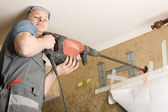 Technician air conditioning drills the wall — Stock Photo