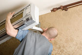 Air conditioning master installs a new air conditioner — Stock Photo