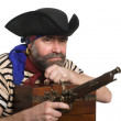 Pirate with a musket holding a chest — Stock Photo #5754334