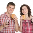 Happy girl and a guy eating hamburgers — Stock Photo