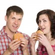 Girl and a guy eating hamburgers — Stock Photo