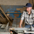 Carpenter working on woodworking machines - Stock Photo