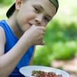 Little boy eating wild strawberries — Stock Photo