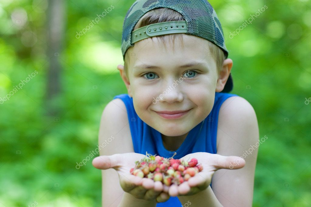 Little boy holding strawberries. Focus on the face of the boy. — Stock Photo #5970427