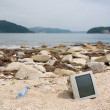 Old computer monitors, bottles on the beach. — Stock Photo
