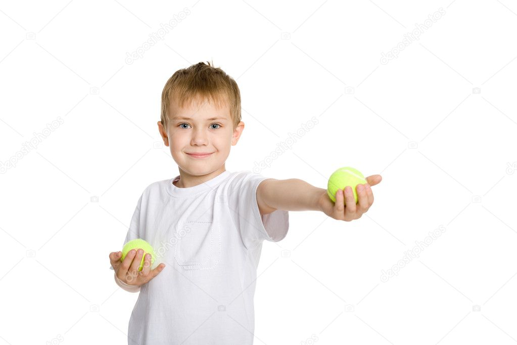 Blond boy playing in the tennis balls. — Stock Photo #6395381
