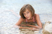 Teenage girl laying in the sea water — Stock Photo