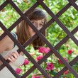 Teenage girl behind a fence — ストック写真
