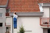 Człowiek na drabinie wspinaczka na dachu — Zdjęcie stockowe