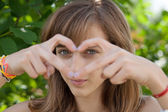 Teenage girl forming heart with her hands — Stock Photo
