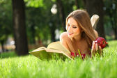 Woman in the park with book — ストック写真
