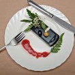Cellular telephone on the white plate, decorated with greens and ketchup — Stock Photo