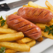 Fried sausage with french fries - Stock Photo