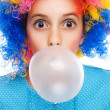 Young girl with clown wig and bubble gum — Stockfoto