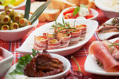 Bacon rolls and other antipasto food — Stock Photo
