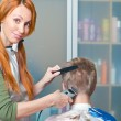 The beautiful young woman the hairdresser does a hairstyle to the client - — Stock Photo #5412383