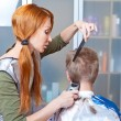 The beautiful young woman the hairdresser does a hairstyle to the client — Stock Photo