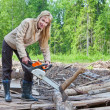 The young woman in wood saws a tree a chain saw — Stock Photo