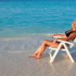 Young pretty woman tans in beach chair, it put in ocean — Stock Photo #5448345