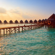 Stock Photo: Island in ocean, overwater villas at time sunset.