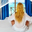 Young pretty woman in bed with ocean behind window. — Stock Photo #5476868