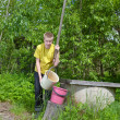 The boy, the teenager, pours water in a bucket from a well — Stock Photo #5476929