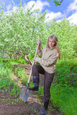 The young woman digs up a garden-bed with the first sprouts — Stock Photo
