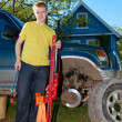 Stock Photo: Young man, teenager replaces wheel at off-road car