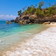View from a sandy beach on rocks at ocean. Indonesia, Bali - Stock Photo
