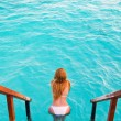Maldives. Young sports woman swims from steps of villa on water - Lizenzfreies Foto