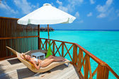 Young woman on chaise lounge under parasol near the sea.Maldives. — Stock Photo