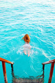 Maldives.Young sports woman swims from steps of villa on water. — Stock Photo