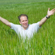 The happy young man in the field of green ear — Stock Photo #6130905