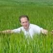 The happy young man in the field of green ears — Stock Photo #6130908