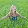 The happy young woman in the field — Stock Photo