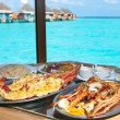 Two plates with lobster on table at window with view on ocean — 图库照片