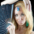 The beautiful young woman with long  blonde hair and  fan and jewellry on — Stock Photo