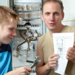 The father and the son-teenager together look the instruction on repair a g — Stock Photo #6589562