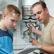Father and son-teenager together look instruction on repair g — Stock Photo #6589564