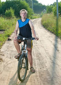 Teenager goes on bicycle on country road — Stockfoto