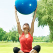 Fitness girl doing exercise with pilates ball outdoors — Stock Photo #5919442