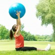 Fitness girl doing exercise with pilates ball outdoors — Stock Photo #5919603