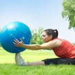 Fitness girl doing exercise with pilates ball outdoors — Stock Photo #5919736