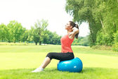 Fitness girl doing exercise with pilates ball outdoors — Stock Photo