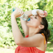 Fitness girl refreshing after exercise outdoors — Stock Photo