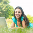 Portrait of beautiful young woman using laptop in the park — Stock Photo